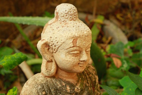 A Sculpture of Buddha with Mold and Moss