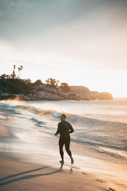 Man in Black Jacket Walking on Beach