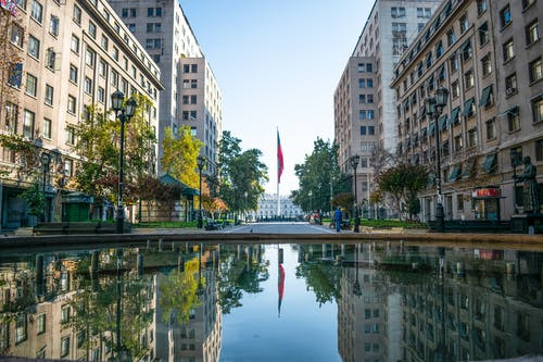 A Reflection of the Buildings and the Flagpole on the Fountain Water