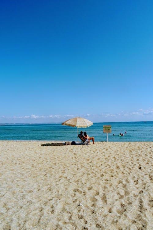 A Couple Sitting Under a Beach Umbrella