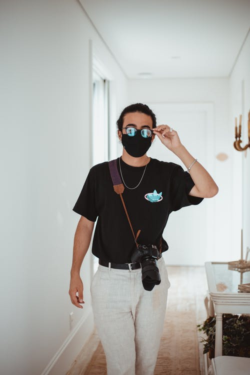 Male photographer wearing casual clothes and protective mask standing with photo camera and adjusting sunglasses while standing in hall