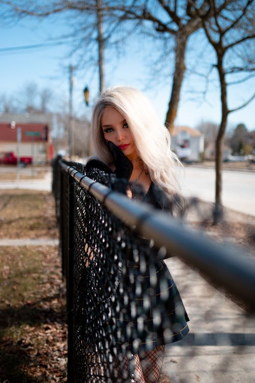 A Beautiful Model Leaning on a Chain-Link Fence