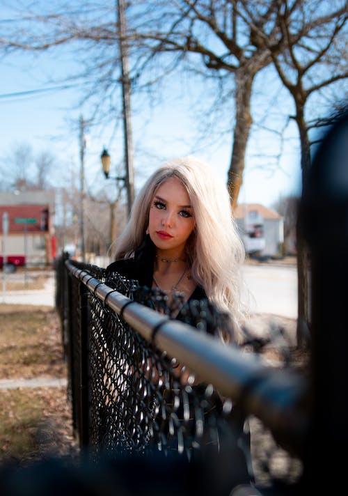 Woman in Black Shirt Standing Beside Black Metal Fence