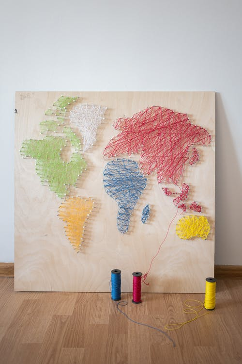 Creative world map created with colorful threads on canvas placed on wooden floor in light workshop