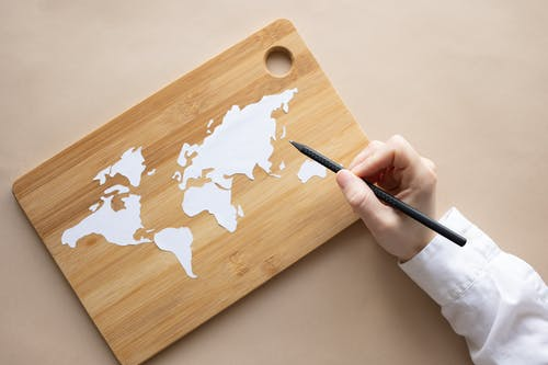 Crop artist with white pencil drawing world map on desk