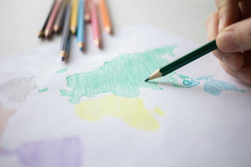 A Person Coloring a World Map Drawing