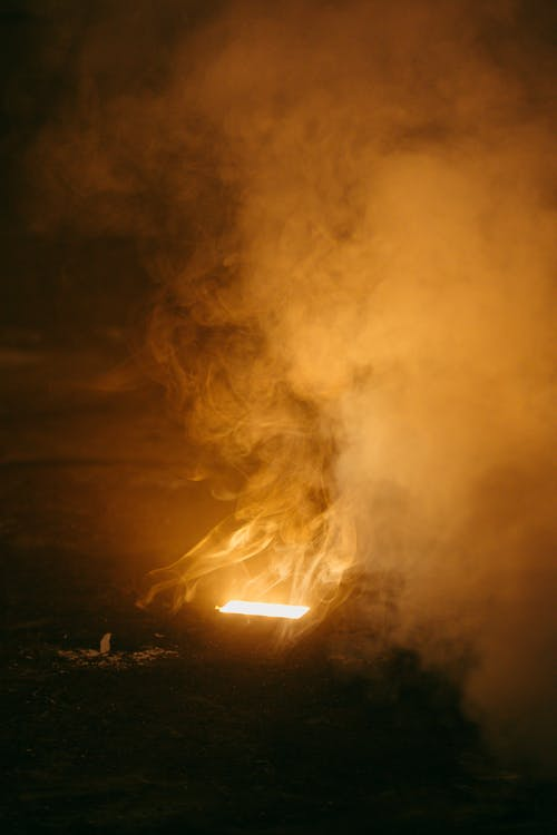 Side view of anonymous person sitting against bright flame under cloud diffusing in air at dusk