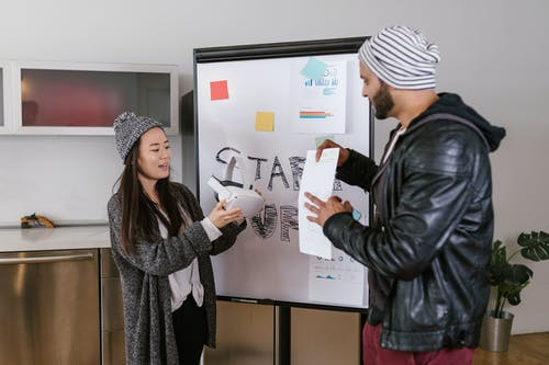 Man and Woman Standing Near the Whiteboard