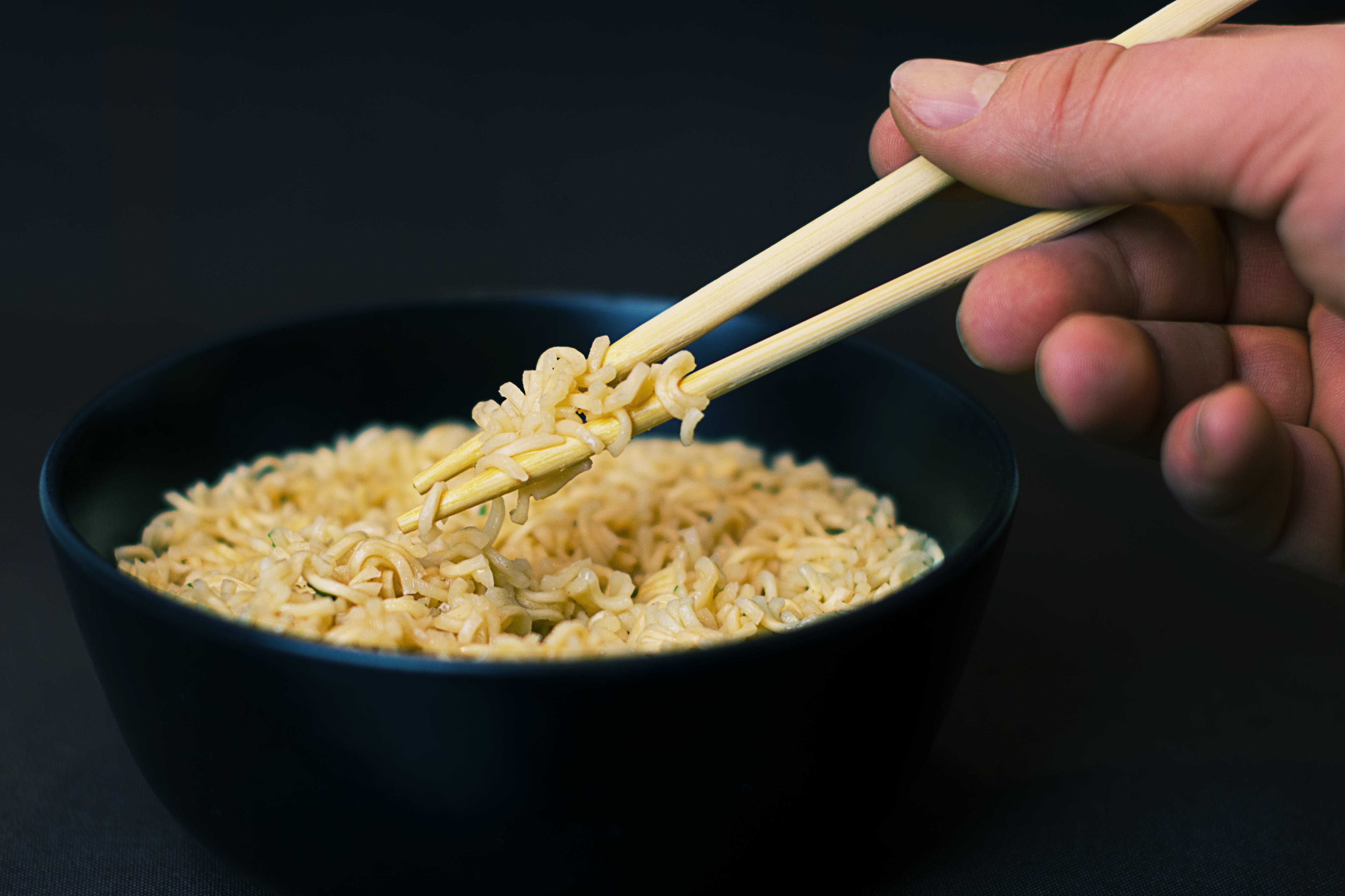 Person Holding a Chopsticks and Picking a Noodles in Black Bowl