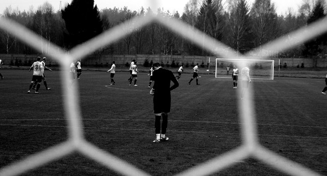View of soccer players through goal net