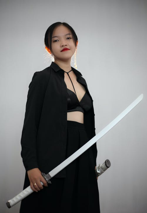 Content Japanese female with katana in hand wearing black outfit with bra looking at camera while standing on white background
