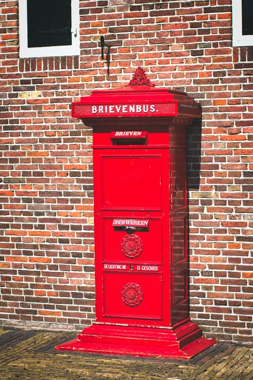 A Red Letterbox beside a Brick Wall