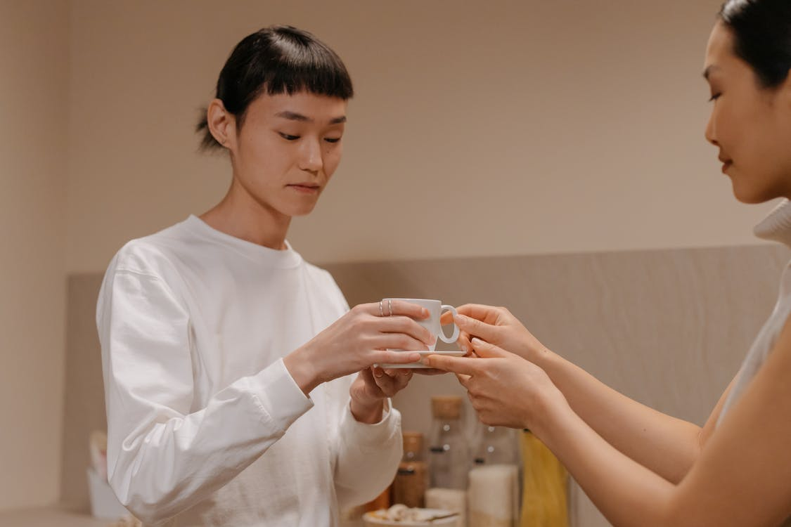 Side view of crop adult Asian woman giving cup of freshly brewed coffee to teenage daughter while standing together in kitchen during breakfast