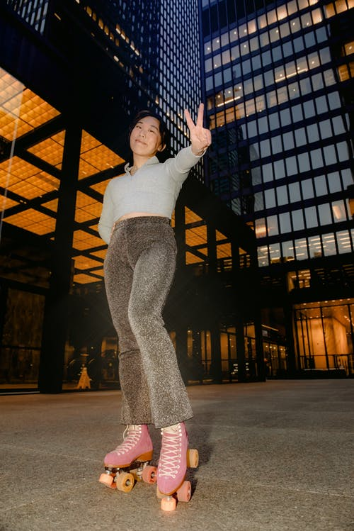 Happy ethnic woman on roller skates showing peace gesture near modern buildings