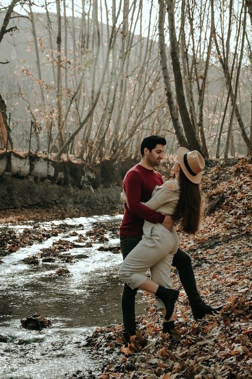 Stylish couple near creek in autumn park