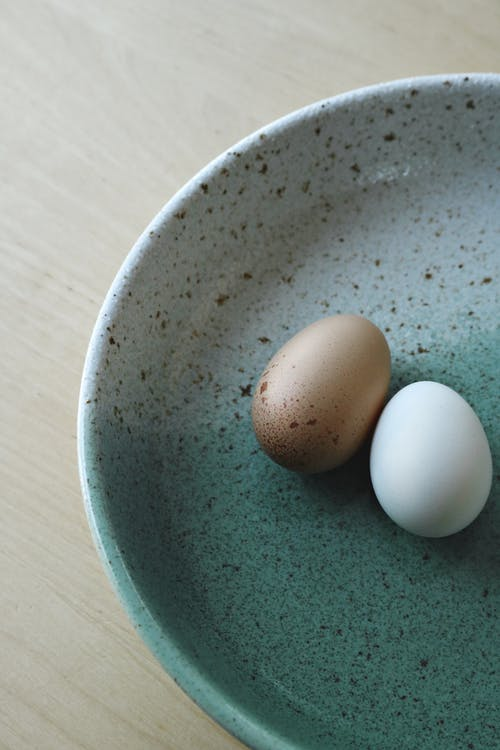 2 White Eggs on Blue Ceramic Bowl
