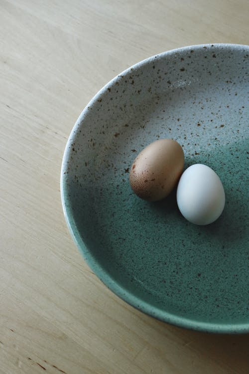 Brown Egg on Blue Ceramic Bowl