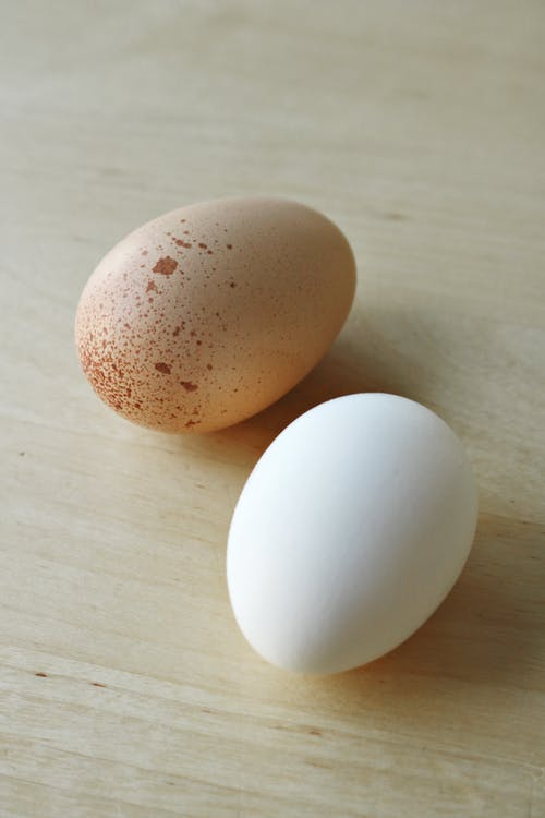 2 White Eggs on Brown Wooden Table