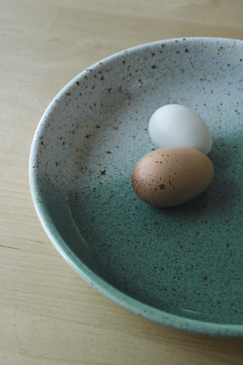 White Egg on Green Ceramic Bowl