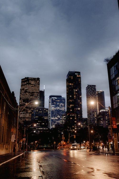 Modern city street with illuminated skyscrapers in rain