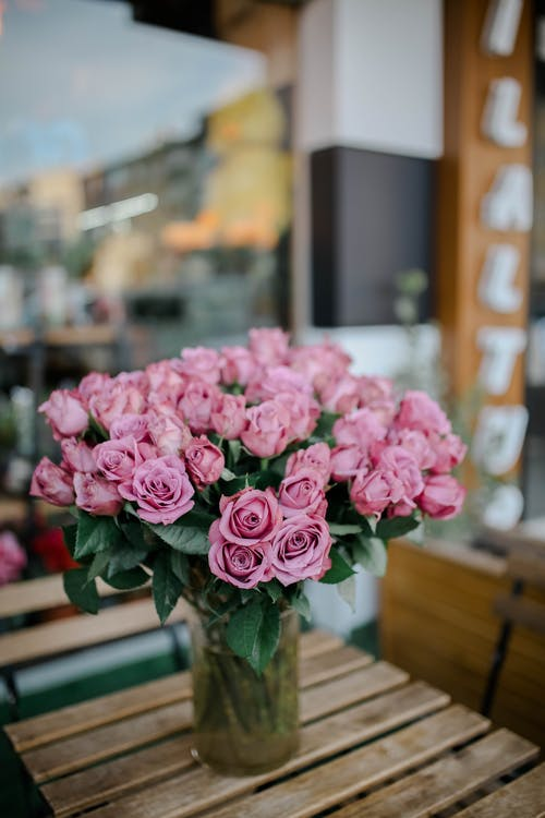 Bouquet of pink blossoming roses in glass vase on wooden table near window on terrace in daytime