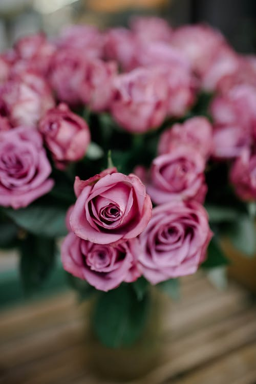 From above bouquet of roses with pink petals and green leaves in vase placed on wooden table on blurred background