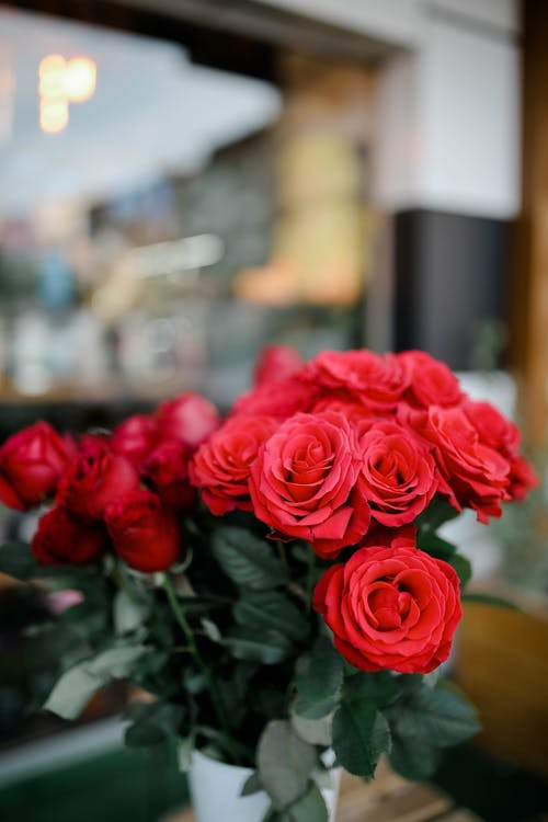 Bouquet of fresh roses with green leaves in vase placed on table near window of building on street on blurred background