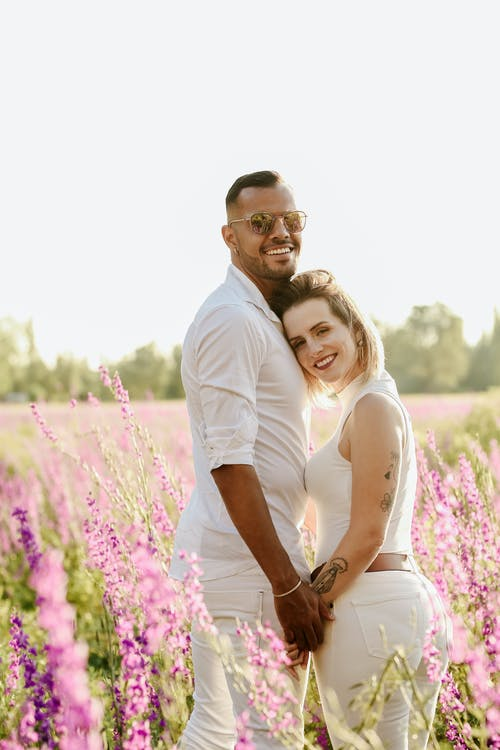 Happy couple hugging in field with flowers