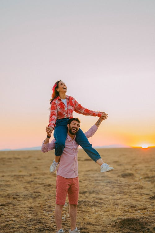 Full body of cheerful man carrying excited girlfriend on shoulders while standing on grassy meadow in nature in evening time
