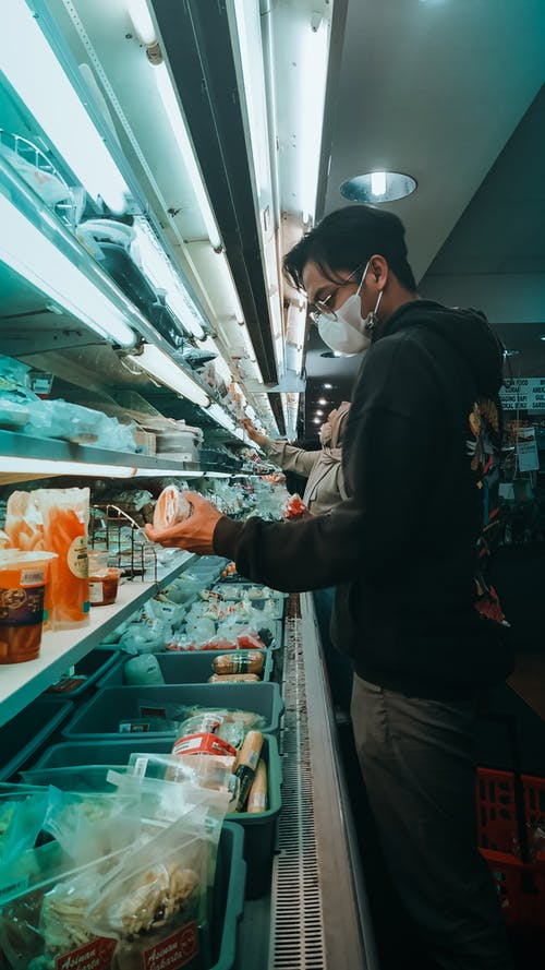 Young ethnic man choosing products from fridge in supermarket