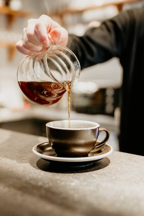 Unrecognizable professional barista pouring freshly brewed coffee from glass pot into cup while standing at counter on blurred background during work