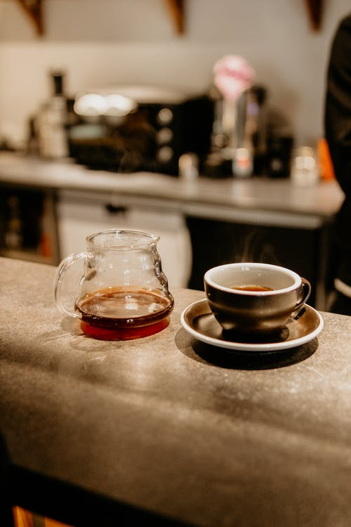 Mug of freshly brewed aromatic coffee near glass pot placed on counter in cafe with modern appliances on blurred background