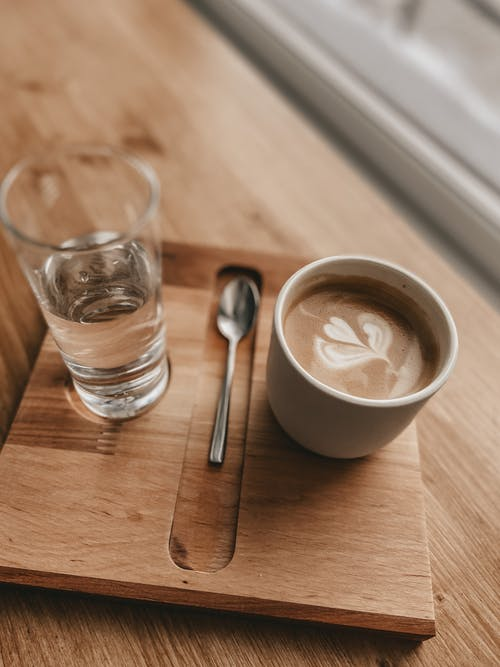 From above of mug with coffee and latte art placed on wooden tray with glass of water and spoon in modern cafe
