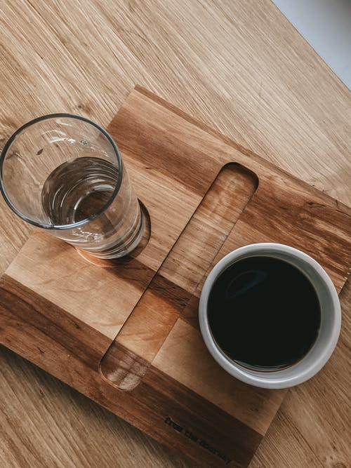 Top view of arrangement of cup of americano and glass of water served on wooden tray on table for making americano for breakfast