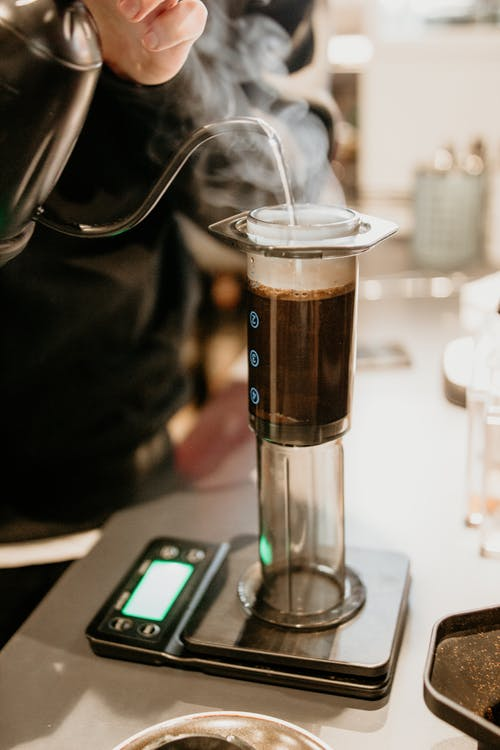 Crop faceless barista pouring hot water into aeropress coffee maker