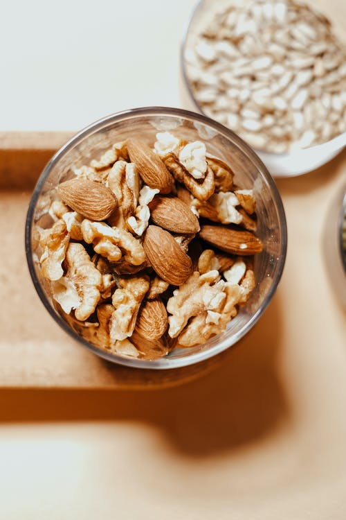 Brown and White Nuts in Clear Glass Bowl