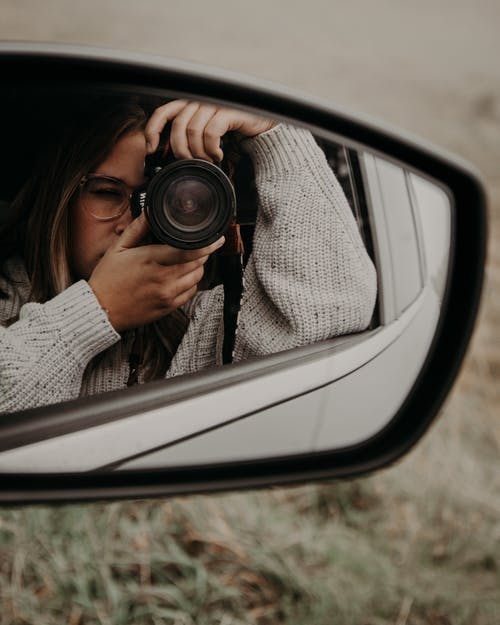 Woman taking photo of side mirror