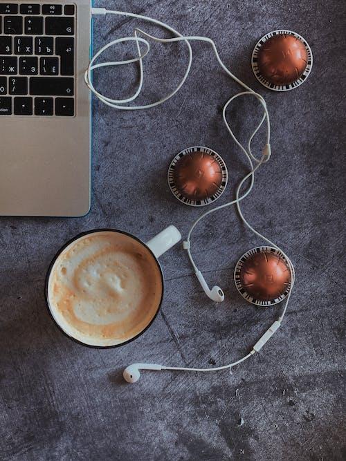 White Ceramic Mug Beside White Earbuds