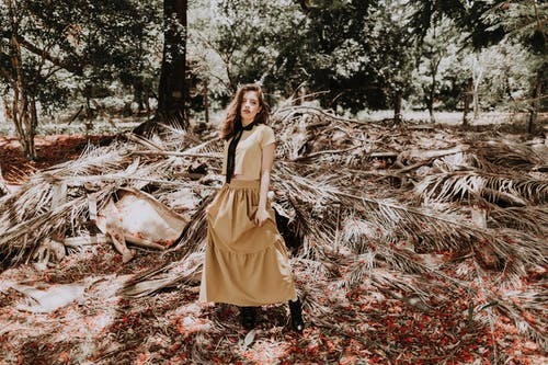 Full body of young female in elegant outfit looking at camera while standing near big faded tree branches in nature