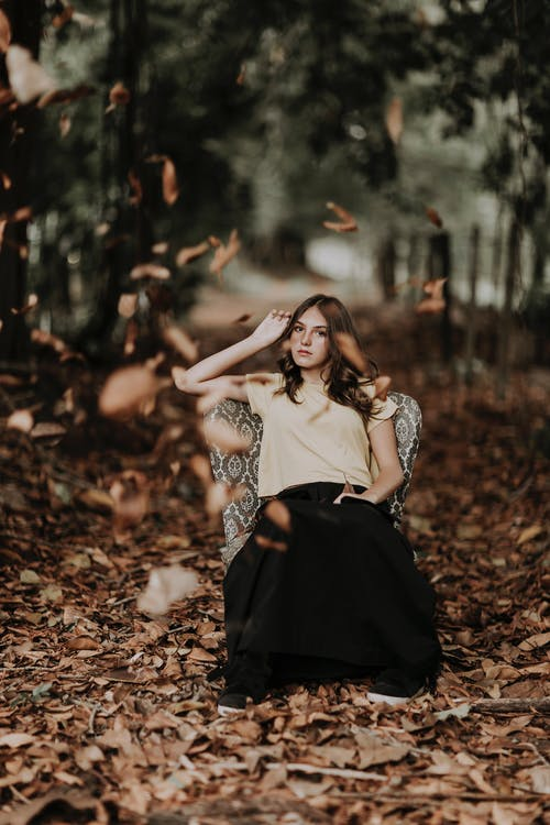 Stylish woman sitting in autumnal forest with falling leaves