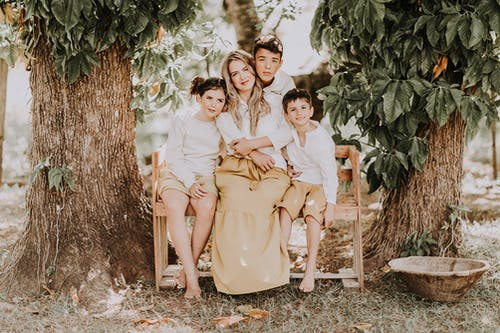 Full body of smiling loving mother with children cuddling together while sitting on wooden bench among green trees in garden in summer countryside