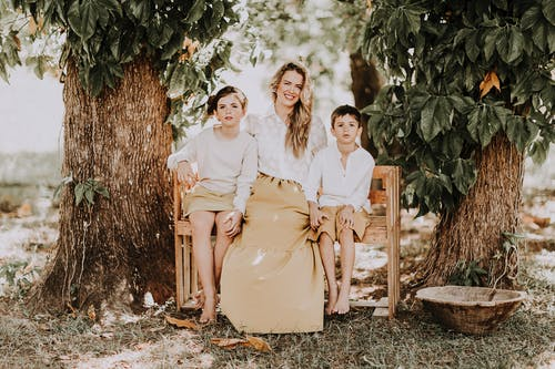 Full body of happy young woman in boho style outfit sitting on bench with son and daughter while enjoying summer day together in rural garden
