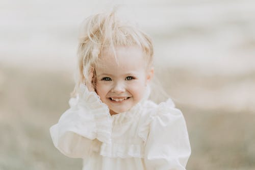 Charming toddler girl with blond ponytail and blue eyes wearing white dress with ruffles smiling and looking at camera against blurred background