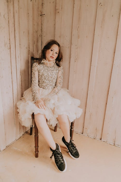 Trendy female teenager in fluffy skirt and gumshoes sitting on chair against ribbed walls while looking at camera
