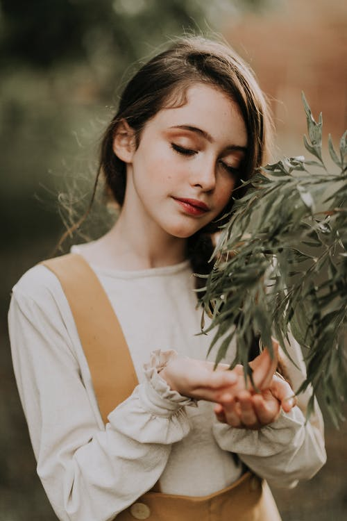 Mindful teen against shrub branch in park