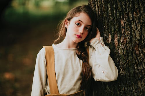 Charming female teenager with red lips leaning on rough tree trunk while looking at camera in park