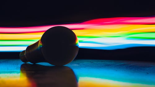 Single light bulb placed on dark surface against abstract background with multicolored rainbow lights in studio with black wall and dim light