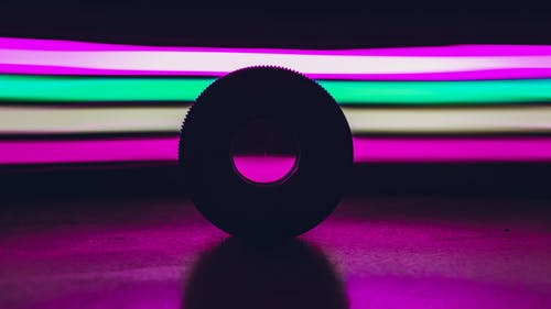 Round disk placed on black surface against abstract background with bright colorful stripes glowing in dark studio with purple illumination
