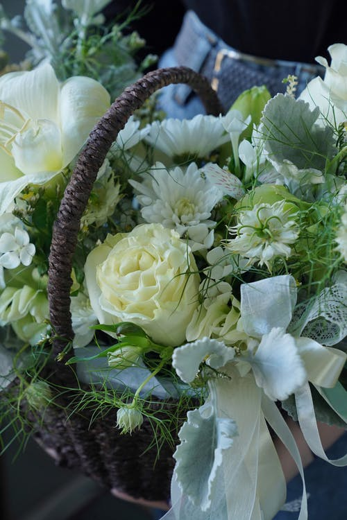 Brown wicker basket with creative composition of fresh white flowers and green leaves
