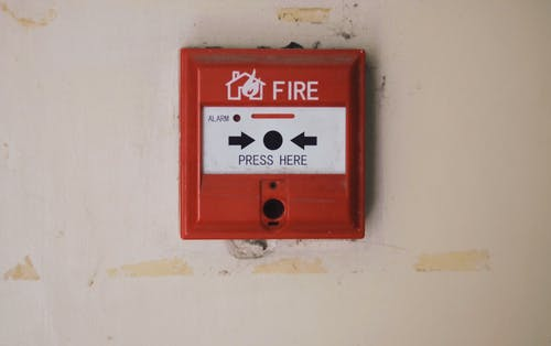 Emergency safety fire detection system box for safety with inscription and push button placed on white wall in light room